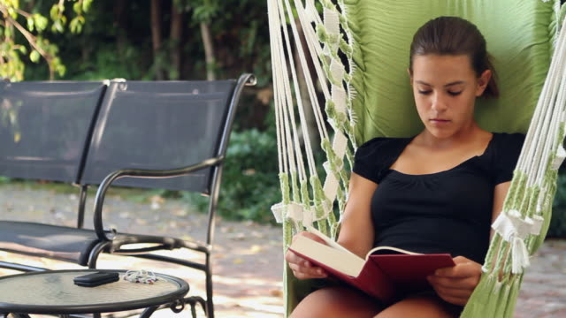 MS PAN Girl (12-13) reading on swing / Buffalo, New York, USA