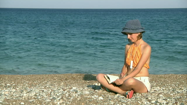 girl reading on the beach - one teenage girl only stock videos & royalty-free footage
