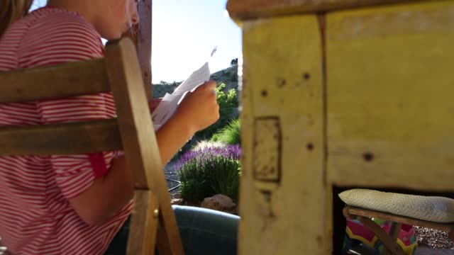 girl reading outdoors - 後ろで束ねた髪点の映像素材/bロール