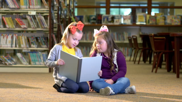 girl reading to friend with down syndrome - primary school child stock videos & royalty-free footage