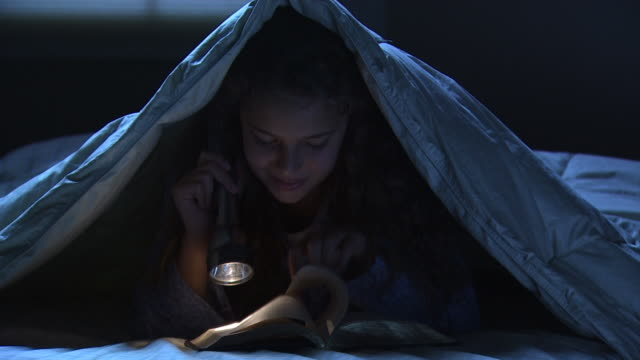 girl reading under the covers - electric torch stock videos & royalty-free footage