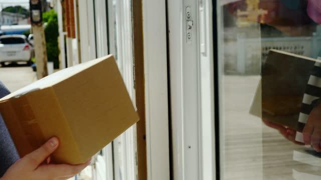vídeos y material grabado en eventos de stock de chica recibiendo paquete de caja marrón del repartidor en casa, concepto de compras en línea. - enviar actividad