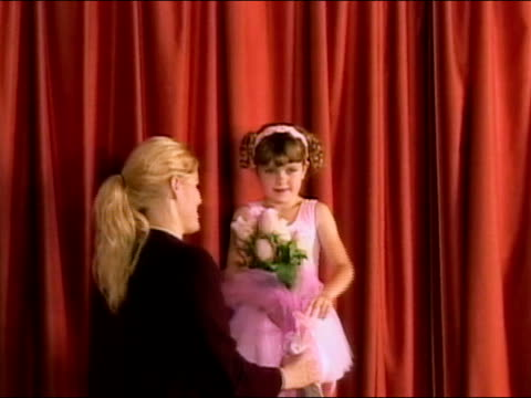 Girl receiving flowers on stage at end of ballet recital / Los Angeles, California