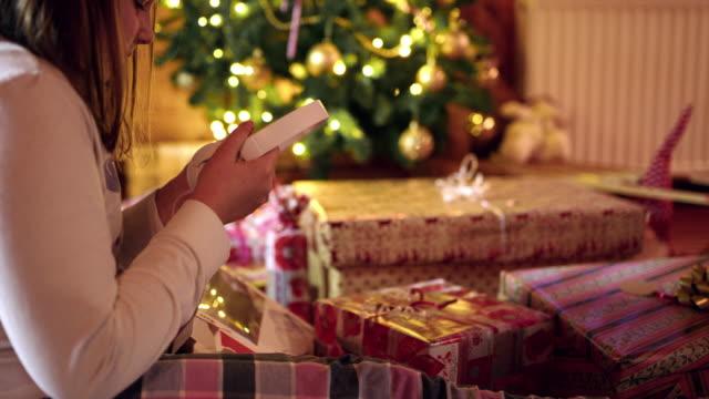 4K Girl receiving headphones Christmas gift near Christmas tree, real time