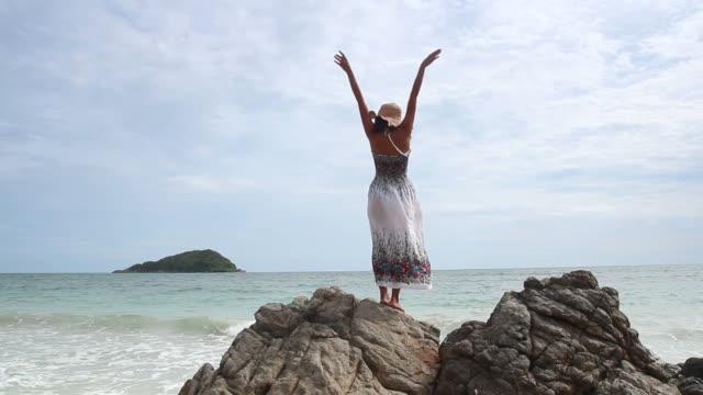 女の子が海の岩の上にリラックスします。 - 美しい女性点の映像素材/bロール