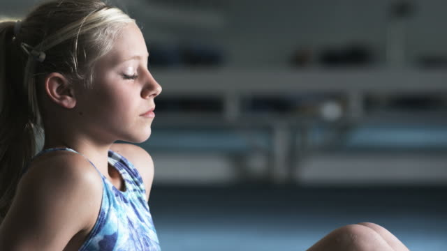 CU TU Girl (10-11) relaxing in gym, Orem, Utah, USA