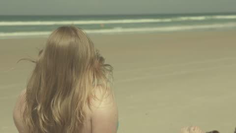 vídeos y material grabado en eventos de stock de girl relaxing on the beach - filtración de luz