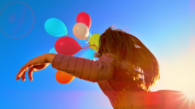 slo mo girl releasing a bunch of colourful balloons into the sky - multi coloured stock videos & royalty-free footage