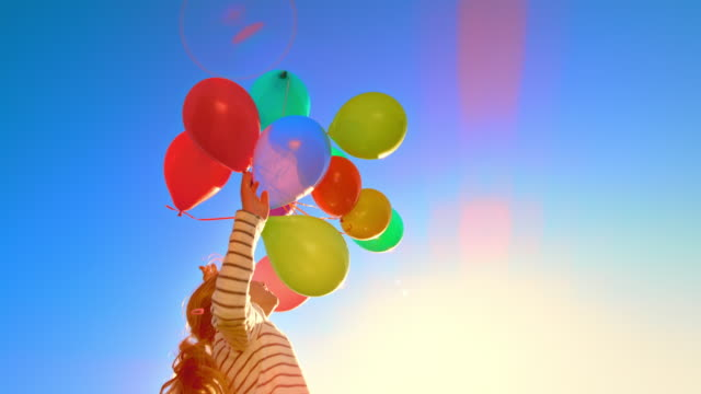 vídeos y material grabado en eventos de stock de slo mo girl lanza globos de colores al aire en un día soleado - globo de helio