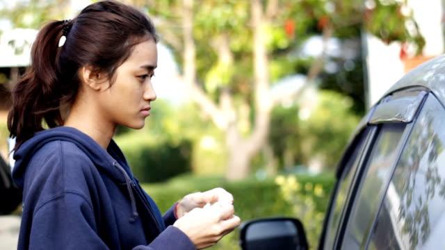 girl remove make up using car mirror