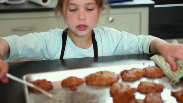 cu focusing girl (6-7) removing fresh baked cookies from \baking sheet on kitchen counter, yarmouth, maine, usa - oven mitt stock videos and b-roll footage
