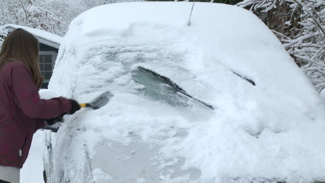 MS Girl removing heavy snow layers from car / Saarburg, Rhineland-Palatinate, Germany