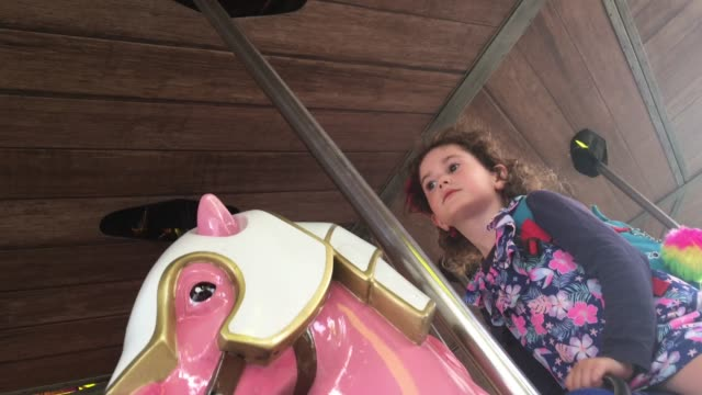 girl ride on horse carousel - carousel horse stock videos and b-roll footage