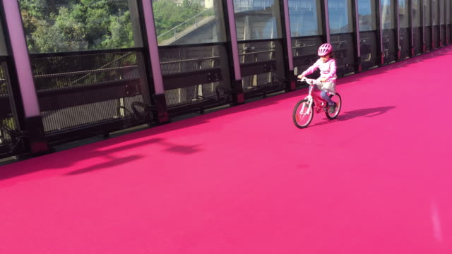 Girl rides bike on pink cycleway in Auckland