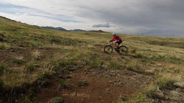 girl rides her mountain bike across a beautiful grass field - スポーツヘルメット点の映像素材/bロール