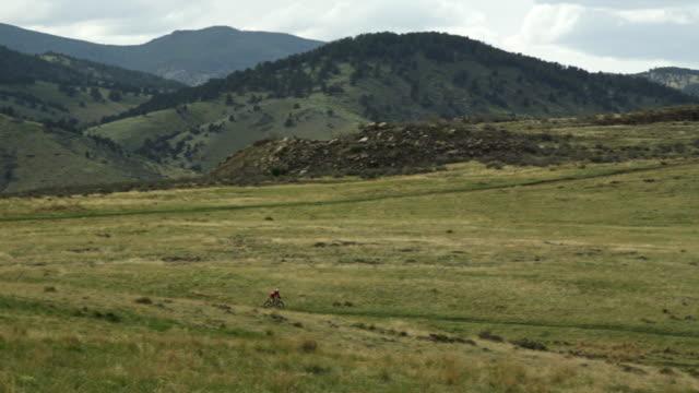 girl rides her mountain bike down a beautiful grass field with mountains in the background - endast en tonårsflicka bildbanksvideor och videomaterial från bakom kulisserna