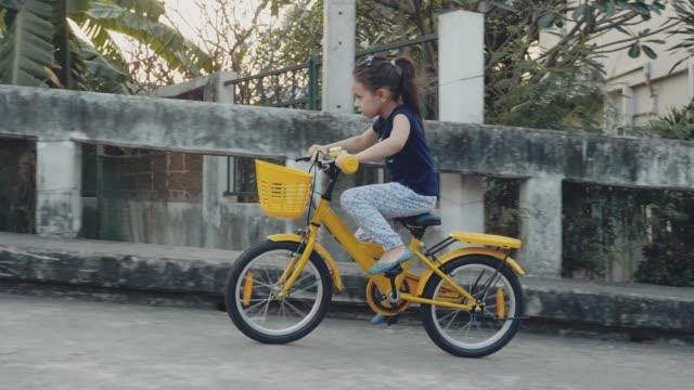 girl riding a bicycle - giallo video stock e b–roll