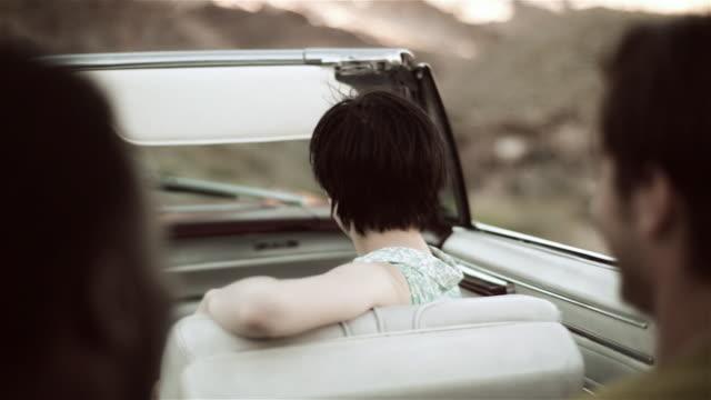 vídeos y material grabado en eventos de stock de girl riding in convertible smiles and laughs with friends - turismo vacaciones