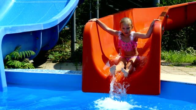 vídeos de stock e filmes b-roll de girl riding in the water park on a water slide - equipamento de parque infantil