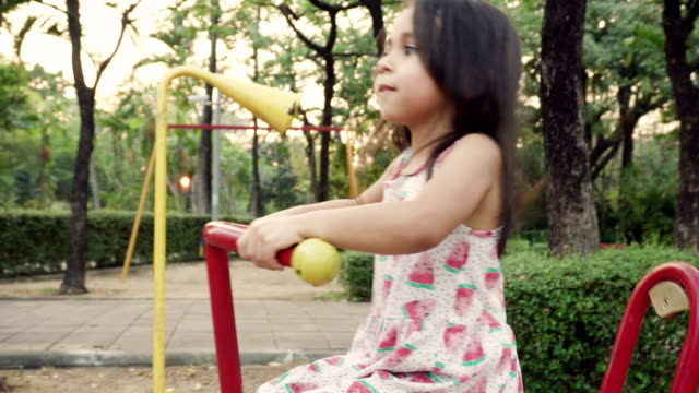 A girl riding on a rocking horse in park