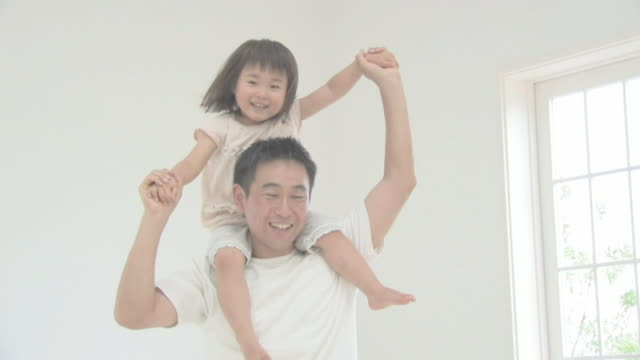 Girl riding on father's shoulders smiling