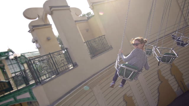 Girl riding the chairoplane in an amusement park