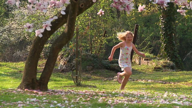 slo mo ws pan girl (8-9) running around magnolia tree, vrhnika, slovenia - vrhnika stock videos and b-roll footage
