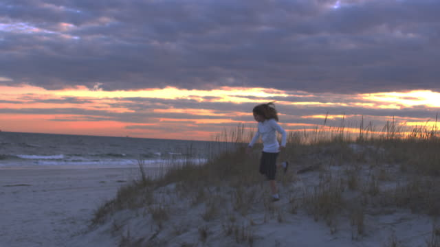 slo mo ws pan girl running down sand dunes and across beach at sunset - oceano atlantico del nord video stock e b–roll