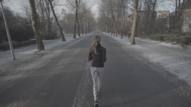 W/S SLOMO STEADY girl running in a park, back