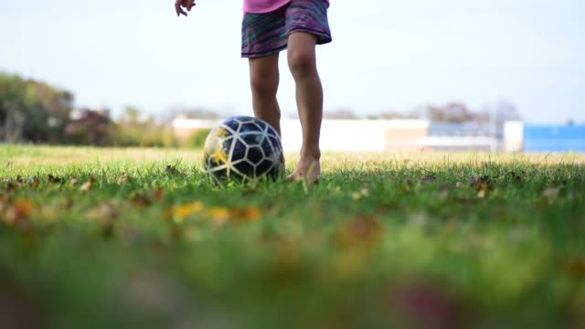 A girl running in a park with a soccer ball.