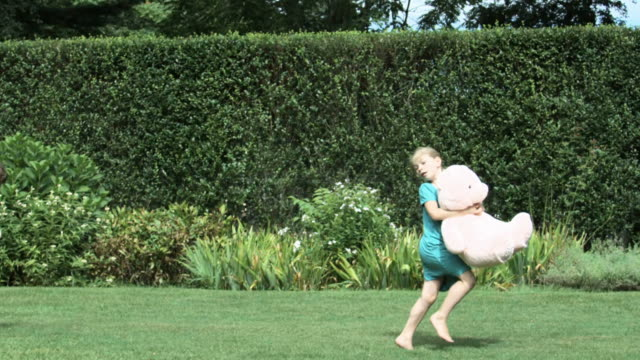 Girl running in garden with soft toy, boy running after her