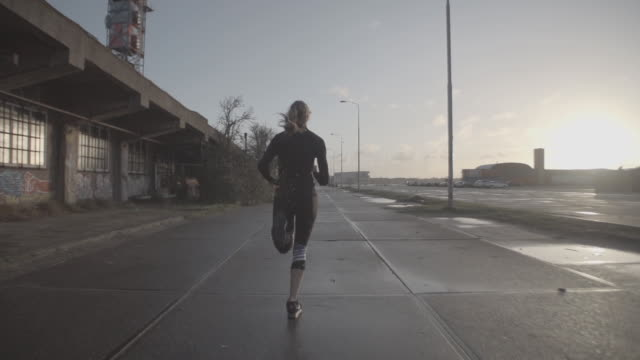 W/S SLOMO STEADY girl running in industrial area, back