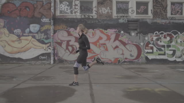 vidéos et rushes de f/s slomo steady girl running in industrial area, side - cadrage en pied