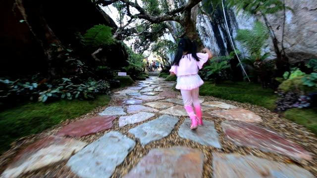 A girl running in the garden.