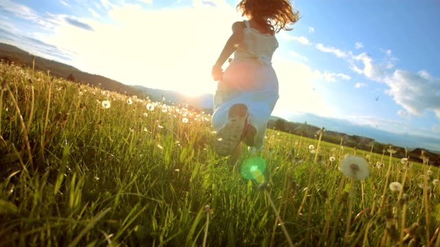 super slo-mo girl running in the meadow at sunset - 花 個影片檔及 b 捲影像
