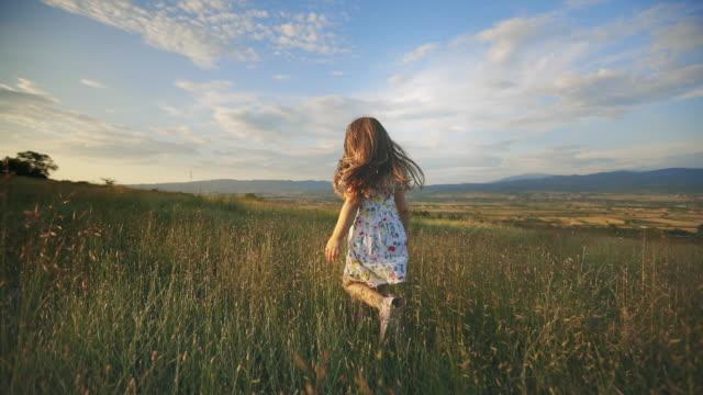 vídeos y material grabado en eventos de stock de chica corriendo en la puesta del sol sobre el campo de hierba - vídeo de stock - multicóptero