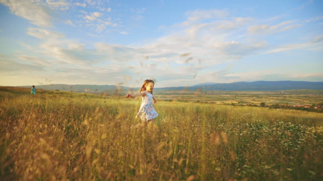 girl running in the sunset over grass field - stock video - elementary age stock videos & royalty-free footage