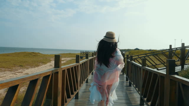 Girl running on a wooden corridor by sea