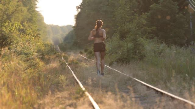 girl running on railways at sunset in forest - joggerin stock-videos und b-roll-filmmaterial