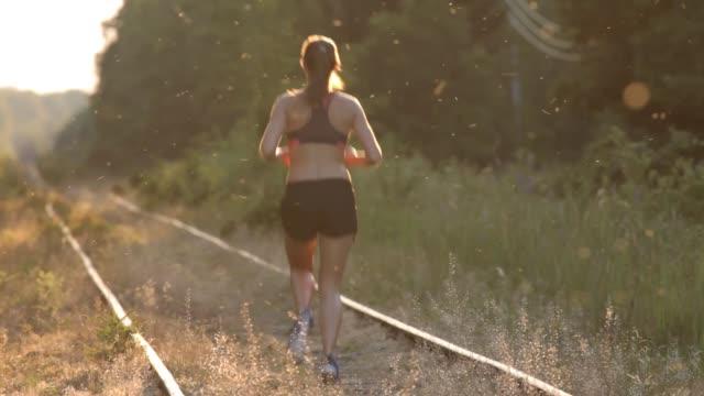 vídeos de stock, filmes e b-roll de girl running on railways at sunset in forest - sutiã para esportes