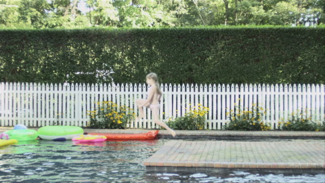 Girl running then jumping into swimming pool in slow motion
