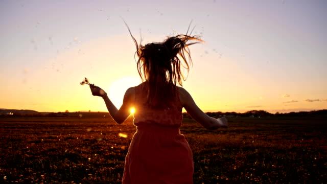 Chica corriendo a través de San Luis Obispo Missouri semillas de diente de león