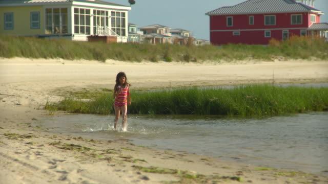 ms pan girl (8-9) running through shallow water on beach, eastville, virginia, usa - eastville stock videos and b-roll footage