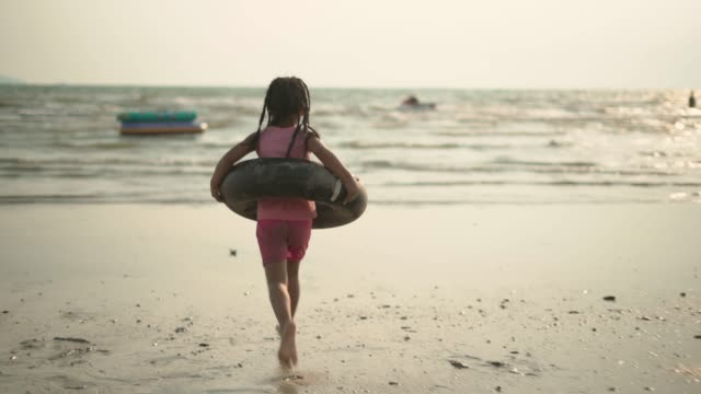 a girl running toward the sea with a flotation tube - following moving activity stock videos & royalty-free footage