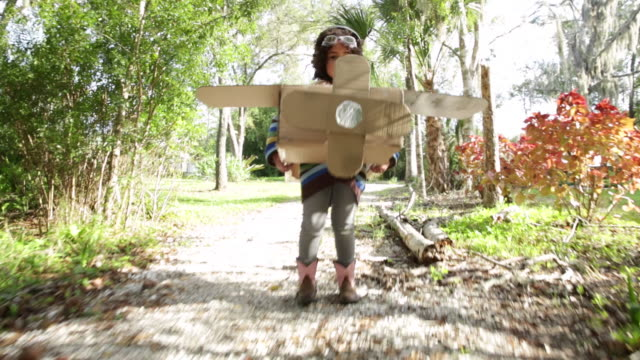TS Girl running, towards camera, over bridge in cardboard aeroplane dressed as pilot.