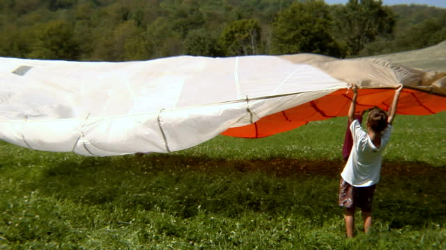 WS Girl running under billowing parachute as three friends stand in field, holding onto edges/ Bovina, New York
