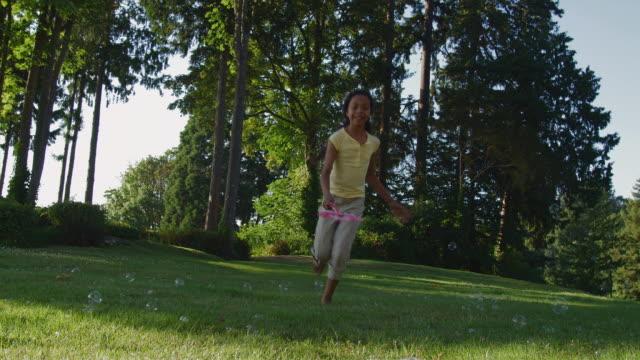 MS Girl (12-13) running with bubble wand in yard / Edmonds, Washington State, USA