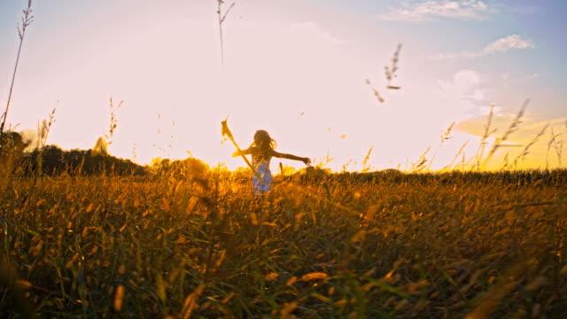 SLO MO ragazza in esecuzione al tramonto con le braccia tese