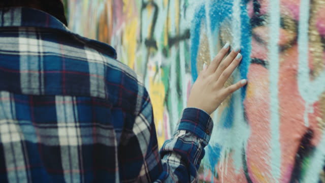 vídeos de stock e filmes b-roll de ms slo mo. girl runs hand along colorful graffiti wall. - muro circundante