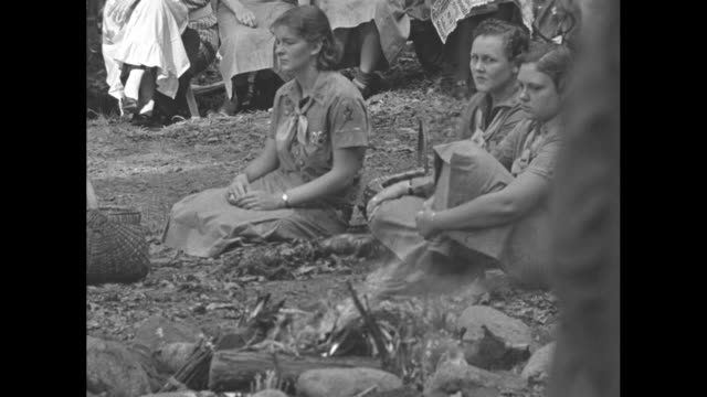 Girl Scouts and guests sitting in circle around Girl Scouts standing around campfire at Jamboree / CU three Girl scouts sitting at campfire / Eleanor...